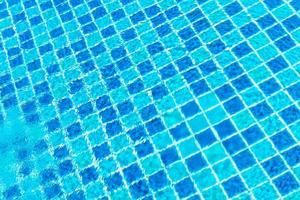Swimming pool tiles with water surface for background photo