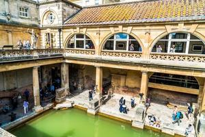 BATH, ENGLAND - AUG 30, 2019 - Roman Baths, the UNESCO World Heritage site with people, which is a site of historical interest in the city of Bath, United Kingdom. photo