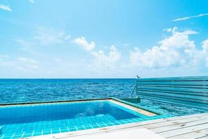 Swimming pool with ocean and sea background in Maldives photo
