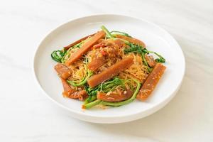 Fideos de arroz salteados y mimosa de agua con calamares en escabeche foto
