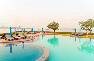 Chair pools or bed pools and umbrellas around swimming pool with sea beach background photo