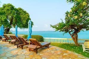 Chair pools and umbrellas around swimming pool with coconut palm trees - Holidays and vacation concept photo