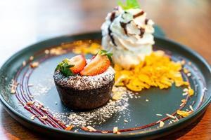 Pastel de chocolate lava con helado de fresa y vainilla sobre placa negra foto