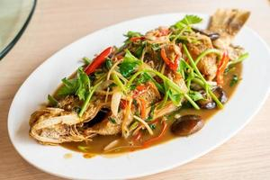 Deep-fried sea bass fish with sweet sauce and trimmings - Asian food style photo