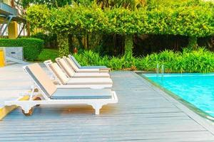 Chair pools around swimming pools in hotel resort - holidays and vacations concept photo