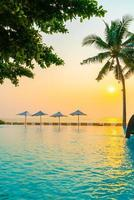 Umbrella and chair around swimming pool with sea ocean view photo
