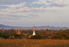 Bagan pagodas fields behind gloden moor with mountain background under cloudy blue sky in the morning photo