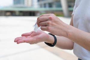 Joven asiática con máscara facial como guía de distanciamiento socialbaila usando gel desinfectante para limpiarse las manos para prevenir el brote de covid-19 o coronavirus. nuevo concepto de estilo de vida normal foto