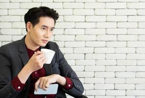 A young asian businessman with confident face is drinking coffee in the break time photo