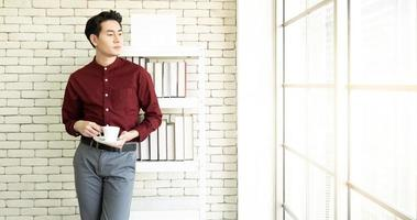 A young handsome asian businessman with confident face standing besides the windows in the working office photo