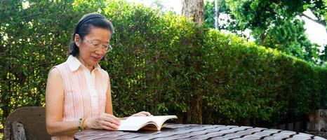 Senior asian woman wearing eyeglasses sitting in the garden reading book in the summer. self development and new normal lifestyle concept photo
