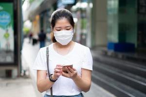 Joven asiática con mascarilla usando un teléfono inteligente y caminando en la ciudad durante el brote de covid-19 o coronavirus. distanciamiento social y nuevo concepto de estilo de vida normal foto