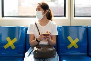 joven asiática con mascarilla, usando un teléfono inteligente y sentada en el tren del cielo. Mantiene el distanciamiento social de otras personas durante el brote de covid-19 o coronavirus. foto