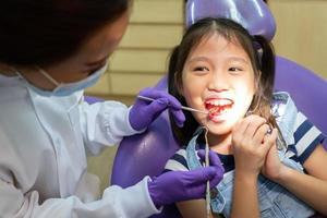 dentista que usa herramientas dentales para limpiar los dientes de un niño asiático y tratar la caries dental en la clínica con ayuda de pie detrás del paciente. concepto de odontología y salud foto