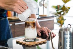 Young man pouring coffee into a glass that contained iced milk. barista and coffee shop concept photo
