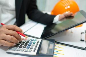 Asian accountant working and analyzing financial reports project accounting with chart graph and calculator in modern office,finance and business concept. photo