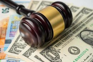 Gavel for judge lawyer on US dollar and Euro banknotes, finance concept. photo