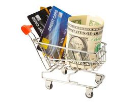 Credit card and US dollar banknotes in shopping cart isolated on white background, finance concept. photo