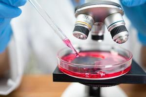 bioquímico científico asiático o microbiólogo que trabaja en la investigación con un microscopio en el laboratorio. para proteger el brote de coronavirus covid19, bacterias y gérmenes. foto