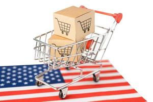 Box with shopping cart logo and USA America flag, Import Export Shopping online or eCommerce finance delivery service store product shipping, trade, supplier concept. photo