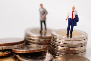La gente en miniatura del hombre de negocios se para en la moneda y la calculadora, concepto de las finanzas del negocio de la gestión. foto