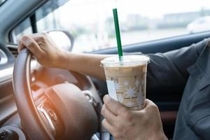 Asian lady holding ice coffee in car dangerous and risk an accident. photo