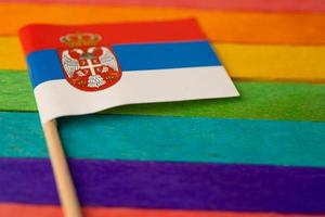 Serbia flag on rainbow background flag symbol of LGBT gay pride month  social movement rainbow flag is a symbol of lesbian, gay, bisexual, transgender, human rights, tolerance and peace. photo