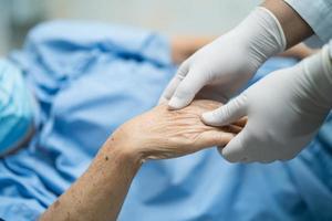 médico sosteniendo la mano del paciente asiático con mascarilla para proteger el coronavirus covid-19. foto