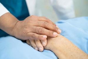Doctor tocando la mano asiática mayor o anciana anciana paciente con amor, cuidado, ayuda, aliento y empatía en la sala del hospital de enfermería, concepto médico fuerte y saludable foto