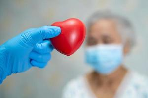 Doctor holding red heart with Asian senior or elderly old lady woman patient wearing a face mask in hospital for protect infection Covid-19 Coronavirus. photo