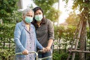 Asian senior or elderly old lady woman wearing a face mask new normal in park for protect safety infection Covid-19 Coronavirus. photo