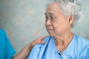 médico asiático de la enfermera fisioterapeuta que toca el paciente asiático mayor o mayor de la mujer anciana con amor, cuidado, ayuda, aliento y empatía en la sala del hospital de enfermería, concepto médico fuerte y saludable. foto