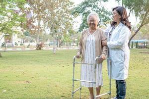 médico ayuda y cuidado anciana asiática anciana o anciana usa andador con una salud fuerte mientras camina en el parque en felices vacaciones frescas. foto