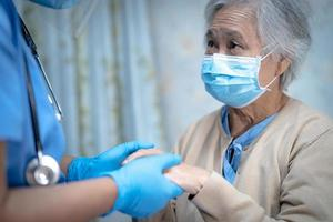 Asian senior or elderly old lady woman patient wearing a face mask new normal in hospital for protect safety infection Covid-19 Coronavirus. photo