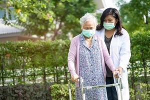 Doctor help Asian senior or elderly old lady woman walk with walker and wearing a face mask for protect safety infection and kill Novel Coronavirus Covid-19 virus. photo