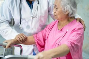 Doctor help and care Asian senior or elderly old lady woman use walker with strong health while walking in hospital. photo