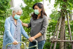 Asian senior or elderly old lady woman walk with walker and wearing a face mask for protect safety infection and kill Novel Coronavirus Covid-19 virus. photo