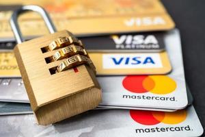 Bangkok, Thailand - July 1, 2020 Golden security digital password lock key on visa master card background. photo
