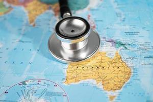 Bangkok, Thailand - June 1, 2020 Stethoscope on Australia world globe map background. photo