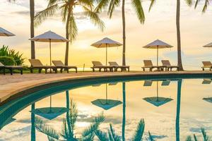 Umbrella and chair around swimming pool in resort hotel for leisure travel and vacation neary sea ocean beach photo