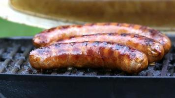 Turning sausages on grill close up video
