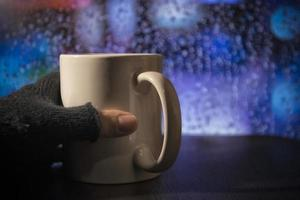una mano con guante con una taza durante la lluvia foto