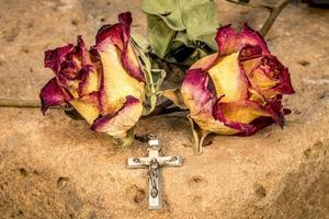 Christian cross on rosary and a dry yellow red roses photo