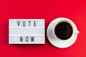 Vote now. Sign and cup of coffee on red background. Election voting concept. photo
