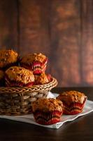 Muffins with raisins on a wooden background. Cupcake in a paper mold on a white napkin. photo
