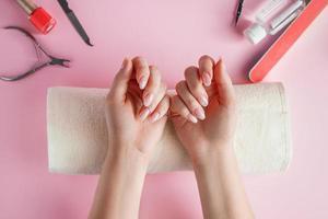 procedimiento de cuidado de uñas en un salón de belleza. manos femeninas y herramientas para manicura sobre fondo rosa. concepto de cuidado corporal spa. foto
