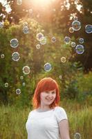 mujer joven con una camiseta blanca está jugando con pompas de jabón. feliz pelirroja bajo el sol. foto