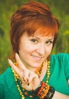 Happy young woman shows victory hand. Red-haired hippie girl in nature. International Day of Peace photo
