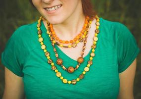 Portrait of happy smiling young girl in nature. Beautiful multi-colored necklaces. photo