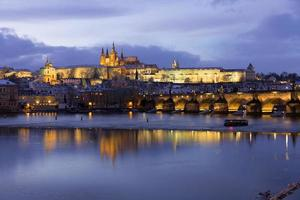 Night colorful snowy Christmas Prague Lesser Town with gothic Castle and Charles Bridge, Czech republic photo